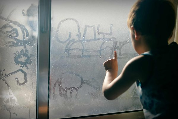Child drawing with finger on a foggy window